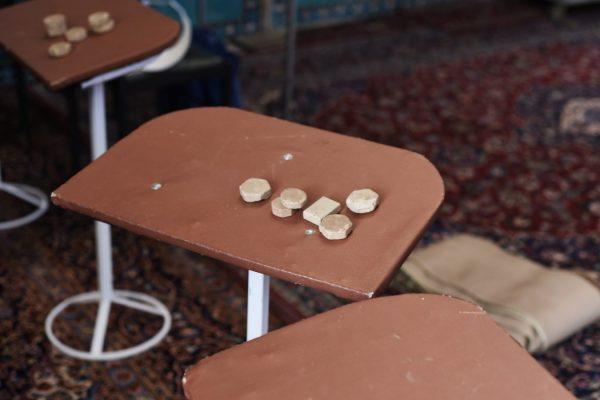 Auf einem Tisch in der Freitagsmoschee von Yazd liegen aus Erde gepresste Gebetssteine.
