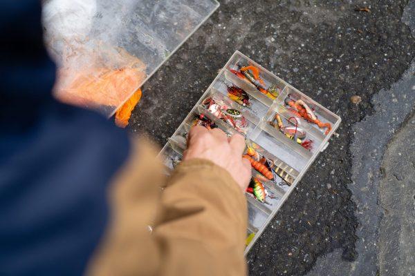 Er greift in die Köderbox, wo bunte Kunstköder liegen, die kranke oder fliehende Fische imitieren.