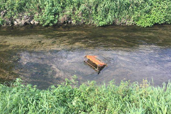 Immer wieder fällt großer Müll auf, der fast wie ein Kunstwerk im Fluss drapiert ist - hier ein Campingstuhl.